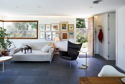 Indirect lighting and slate-flagged floor in modern living room with long corner window and open front door