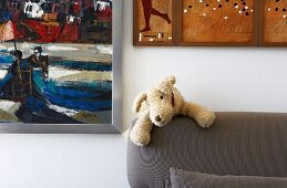 Small plush dog on back of upholstered sofa and various paintings on wall