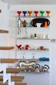 Colourful, postmodern kitchen utensils on stainless steel kitchen shelves
