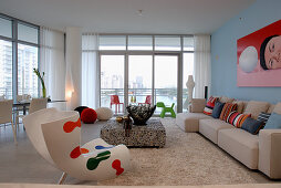 Bright living room interior with bold accents of colour and view of Miami through large windows