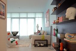 Living room decorated with modern designer objet - elegant floating shelving and pale sofa in background