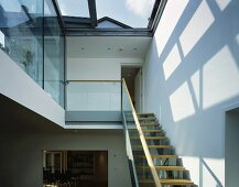 Staircase under glass roof with patterns of light on wall