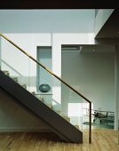 Contemporary staircase in bright stairwell with ceiling-height doorway to corridor