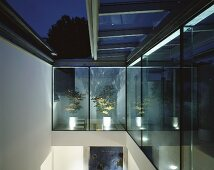Double-height room with sliding glass roof and view of night sky