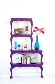 Books and blue glass vases on antique-style tables halved, painted purple and stacked to make decorative shelves