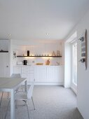 White wooden kitchen in rustic Scandinavian style with 50s chairs and skateboard on wall