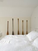 Double bed with snow-white covers and old boat paddles as decoration in traditional attic bedroom
