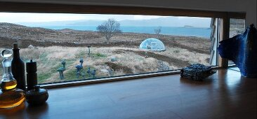 View of barren coastal landscape with sculptures and dome-shaped greenhouse through horizontal kitchen window