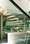 Open wooden staircase with glass stringer and steel girder in front of concrete kitchen in contemporary solar house