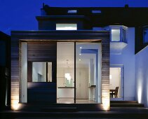 Wood-clad, cubic extension on traditional house at twilight