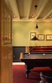 Blick durch offene Tür auf Holz-Billardtisch in schlichtem Zimmer mit weisser Holzdecke und rotem Fußboden.
