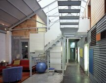Loft-style living space with staircase and corrugated metal cladding on wall