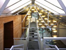 Loft-style living space with metal steps and walkways beneath roof
