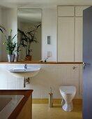 View of modern, white-tiled bathroom through open door
