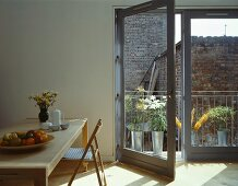 Dining area next to open balcony door with view of potted plants