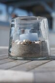Light blue candle on bed of sand and shells in transparent candle lantern