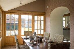 Frühstückstisch mit gradlinigen Korbstühlen in Anbau mit umlaufender Fensterfront