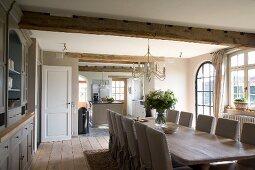 Lange Tafel und Hussen-Stühle im Landhaus-Esszimmer mit anschliessender offener Küche