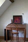Antiker Thonetstuhl an einfachem Holz-Schreibtisch mit buntem Bild
