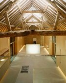 Designer-style, open-plan room in converted house with view of rustic roof timbers and open-plan kitchen below
