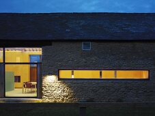 Renovated farmhouse with stone walls at dusk with view of illuminated interior through window
