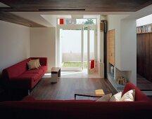 Red sofa set in modern living room with open terrace door