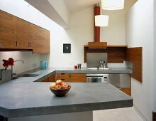 Designer kitchen with wooden doors and concrete work surfaces