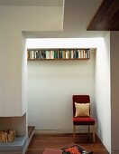 Red upholstered chair in niche next to open fireplace