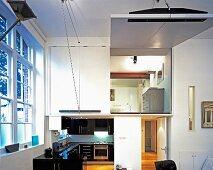 Loftartiger Wohnraum mit Blick in teilweise verglastem Schlafraum auf Galerie