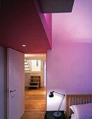 Schlafraum mit teilweise violett getönter Decke über offenstehender Tür und Blick auf Treppe