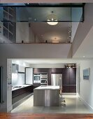 View into kitchen with stainless steel island and upper storey