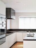 Kitchen island in front of designer fitted kitchen