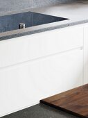 Flush-fitted hob in grey stone work surface
