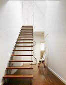 Designer staircase with wooden treads and stainless steel handrail in minimalist, open-plan stairwell