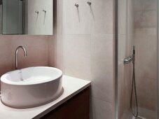 Designer washstand with white basin in niche next to shower area