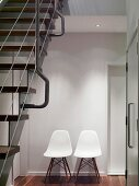 Retro chairs with white, plastic shell seats against wall in modern stairwell