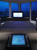 Flat-screen TV at foot of double bed in front of panoramic window with view of city at night