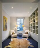 Fitted shelving and seating area in front of window in narrow room
