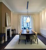 Dark, modern dining table below cubist lightshades in traditional setting