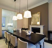 Modern dining area with pendant lamps in front of traditional fireplace beneath gilt-framed mirror