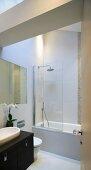 View through open door of bathtub with shower head behind glass partition in modern bathroom