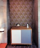 Small sideboard in niche against patterned fabric