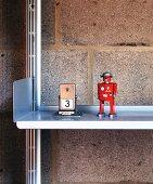 A Playmobil figure next to a retro day calendar on an aluminium shelf against a brick wall