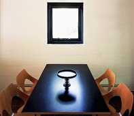 Purist room with perforated wooden shell chairs and ornamental platter on dark table