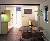 Open-plan, pastel yellow fitted kitchen with light dining furniture and industrial-style wall lamp
