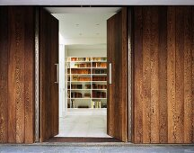 An open door in a wooden wall with a view onto a book shelf