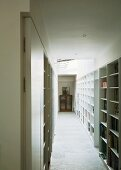 Corridor with white, fitted shelving on both sides