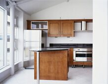 Theke mit schwarzer Granitplatte und Edelstahl-Kühlschrank in moderner Einbauküche mit Holzfronten