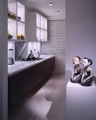 Pair of sculptures with Mongolian features on pedestal in contemporary kitchen with designer appliances