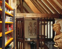 Modern bookcase and antique bust in old, converted barn with historic, wooden-slatted doors